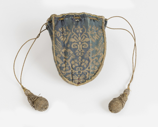 Small purse having four identical shield-shaped panels joined with narrow gold braid; edged at top with same, with a gold cord to draw, whose ends have drops covered in gold netting; lined in rose silk taffeta. Each panel of blue silk with a small-scale symmetrical design woven in gold of a stylized plant with birds perched in the branches, and a winged female figure facing the birds with outstretched hands.