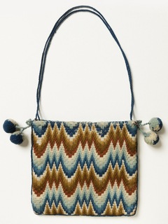 "Small bag embroidered solidly on coarse canvas in wool in Hungarian or ""Flame"" stitch in two browns, two blues, rust red and white. Edged with blue cord and finished with two ball tassels of blue and white wool at the upper corners. Lined with pale green glazed cotton."