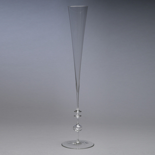 Flat disc-shaped foot; thin stem with hollow sphere and two horizontal flanges; tall flute-shaped body.  Very thin glass.