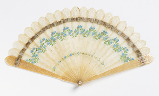 Brisé fan with pierced horn sticks painted with forget-me-nots, laced with a pale silk ribbon. Fan case has removable lid.