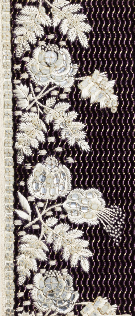 Floral pattern embroidered with white silk and clear glass on ground of purple velvet with wavy purple and yellow lines.