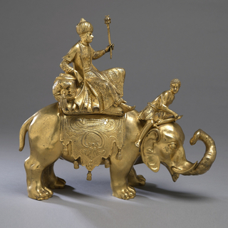 Inkwell in the shape of a turbaned man in robes and holding a scepter, riding on an elephant led by a boy seated on the elephant's neck.