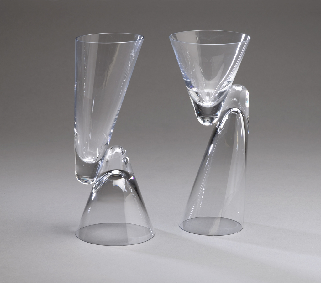 Clear glass form composed of two thin-walled conical bowls, one short and wide, the other long and slightly angled; the bowls facing in opposite directions and joined side-to-side along their thickened vertexes to form a reversible goblet, the mouth of either bowl acting as the base when upside down.  Pair with 1986-36-1.