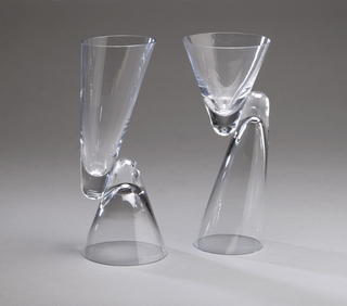 Clear glass form composed of two thin-walled conical bowls, one short and wide, the other long and slightly angled; the bowls facing in opposite directions and joined side-to-side along their thickened vertexes to form a reversible goblet, the mouth of either bowl functioning as the base when upside down. Pair with 1986-36-2.