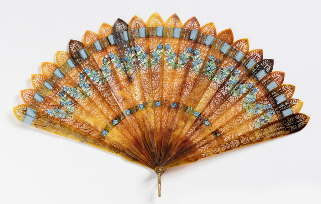 Brisé fan. Brown tortoise shell sticks pierced in flat openwork all-over design. Painted with gouache showing forget-me-nots and sprays of flowers. Blue connecting ribbon.