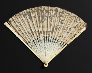 Pleated fan of Brussels-style bobbin lace with scene of figures in a landscape. Pierced, carved and incised ivory sticks and guards.