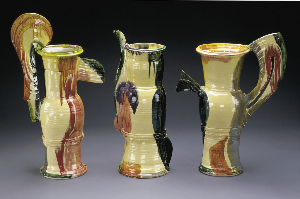 Tall pitcher painted tan, dark green, ochre, and red splotches. Triangular-like applied projection and curved handle with thin cutout.