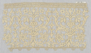 Symmetrical straight edge border in scrolling, flowering vine design made in the seventeenth-century style. Picot edge