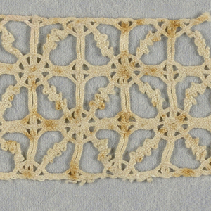 Border fragment of three rows of very small squares filled and connected by linear pattern.