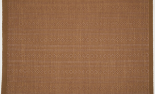 Woven textile resembling basketry, with raised, monochrome diamonds and stripes, in burnt sienna.