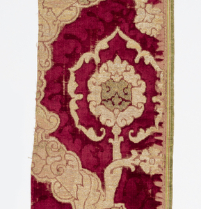 Large-scale pomegranate design within an ogival framework, in red velvet with two pile heights, gold brocading, and some gold in raised loops. May have been part of a chasuble.