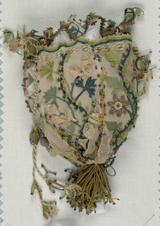 Small bag of cream silk net with elaborate applied design of flowers and leaves in lace stitches. Composed of four panels joined by loose stitches in silk and metal. Gold tassel at bottom, cords to close with gold tassels.