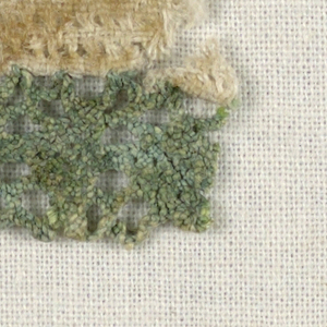 Continuous braid like bobbin lace, dyed green and sewn to plain weave fabric.