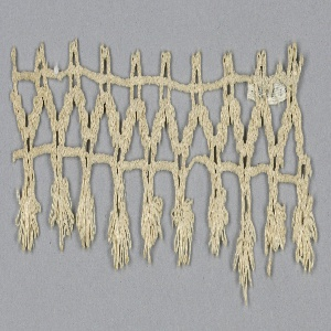 Fragment of edging lace in a zigzag design and trimmed with tassels.