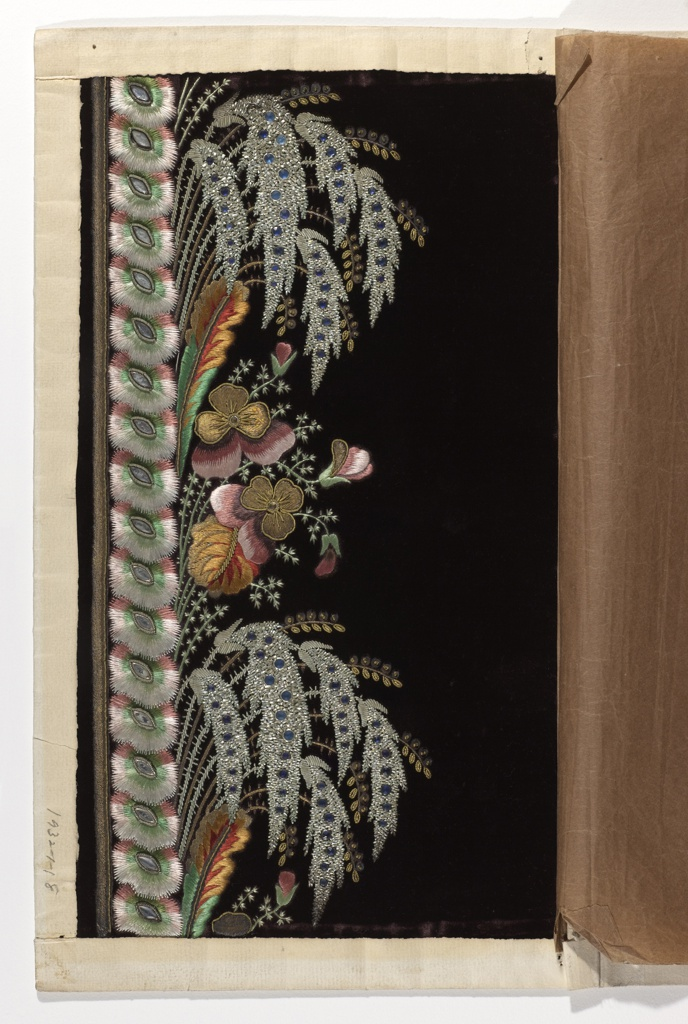Paper envelope containing manufacturer's embroidery sample for a man's long coat. Dark purple cut velvet embroidered in elaborate border design of fern-like leaves worked in silver metal bullion and blue glass; flowers in pink, purple and gold with gold glass centers; and red, orange, green and gold leaves. One edge is bordered with stylized carnation flower heads in pink, white and green with glass and silver bullion centers.