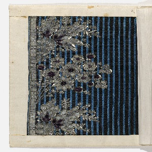 Floral pattern embroidered with white silk, clear and purple glass and silver wire on a vertically striped blue and black ground.