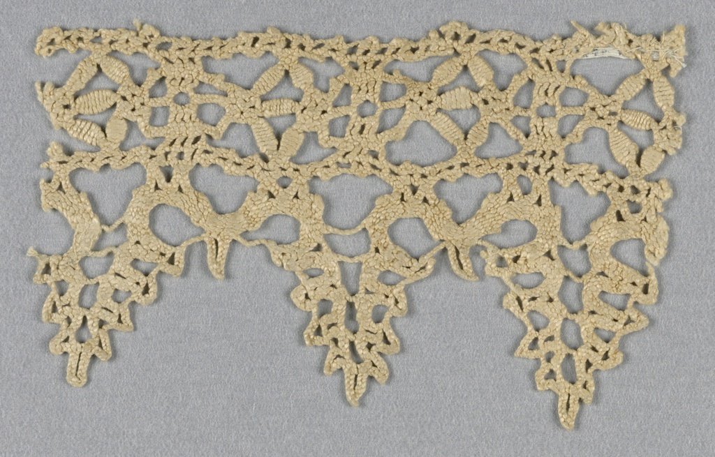"""Fragment of heavy coarse edging lace with points. Small """"seeds"""" in band above points."""
