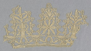 Border fragment of deep points and insertion. Each large point edged with minute points. Alternating points have flower-filled urn, and a minute flower pot above a rosette.