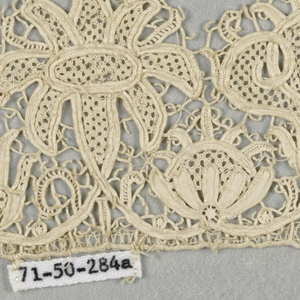 Fragments of a scalloped border formed by two alternating flowerheads. In spaces below flowers are two smaller flowerheads in an alternate arrangement.
