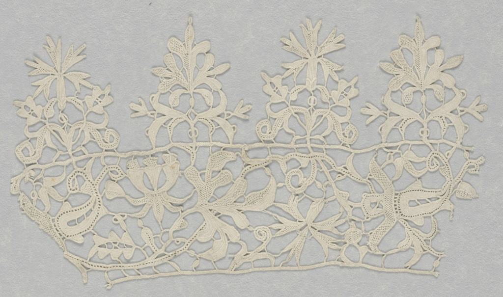 Border of floral serpentines edged on one side by pendants of free floral forms.  Produced by Aemilia Ars.