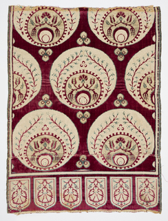 Fragment of velvet with rows of offset circles in creamy off-white on a deep red velvet pile ground. Each circle contains a medallion near its base, encircled by flowering hyacinth branches. Each medallion contains a pearl near its base, encircled by a carnation and tulip on a vine. Trefoil patterns in the interstices. A border at the bottom shows carnations (upside down) enclosed in shield-shaped tabs. In red, off-white and gold with touches of pale green.