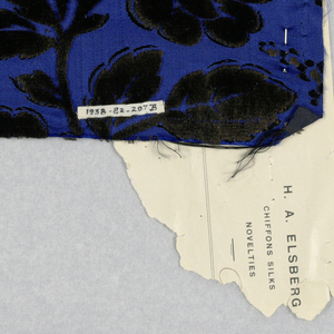 Portfolio with woven fabric samples in a design of slender serpentine stems with large stylized roses in black velvet outlined with short floats of secondary silk weft. Sprays of minute flower in the same technique form serpentine lines that connect to flower heads.