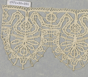 Band fragment has six oval tabs that are filled with radiating floral forms. Below tabs is a staggered scrolling line filled with wheel-like forms.