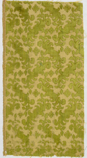 Yellow-green cut and uncut velvet in stylized foliage and flower pattern against a dark yellow ground.
