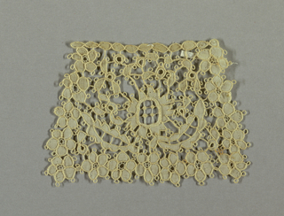 Natural-colored linen with a cut-out design outlined in buttonhole stitches. Border of five-petal blossoms and a central rosette with foliage.