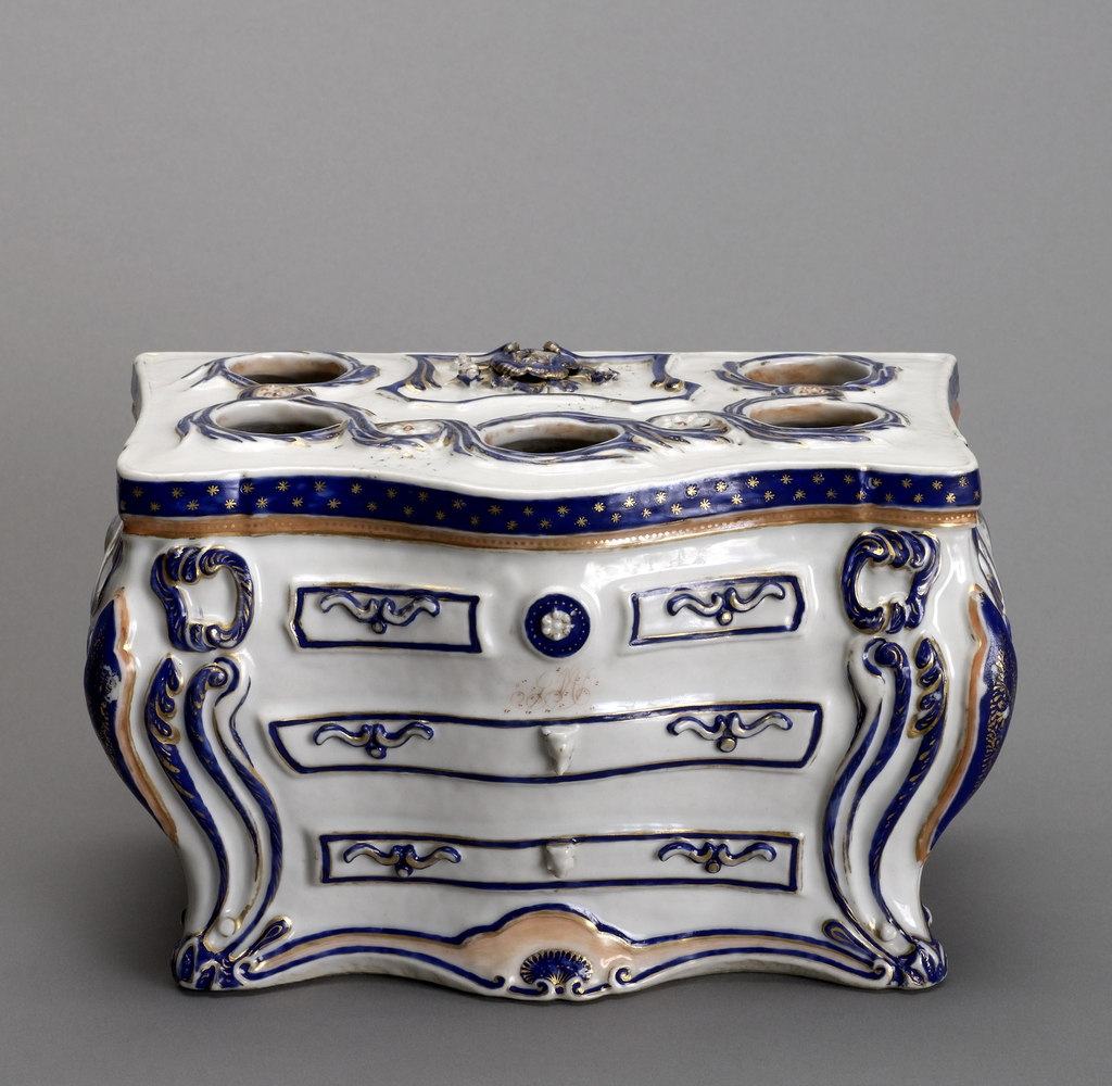 A bulb pot in the form of a commode made in porcelain with gilt detail.