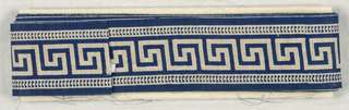 A Greek key border design within guards. In white on blue.