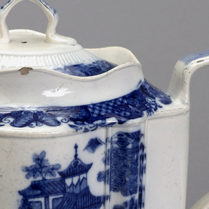 White earthenware teapot and cover decorated with an outdoor garden and gazebo scene in blue.