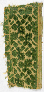 Fragment of cut and uncut dark green velvet in a pattern of leafy sprigs and barrettes on a yellow ground.
