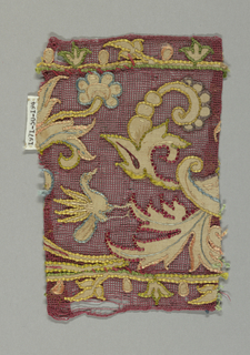 Fragment of a floral band with linen appliqué and multi-colored silk embroidery on red gauze weave.