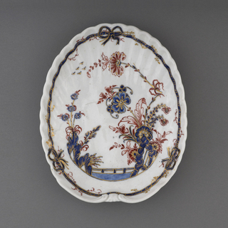 A white oval scalloped dish with a blue ribbon border and a floral pattern within.
