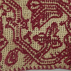 Fragment of a border with a red floral vine pattern on gauze weave.