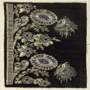 Floral pattern embroidered with multicolored silk and blue, silver and gold glass beads on a patterned black cisele velvet.