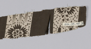 Brown and purple on a white ground in a design of one inch brown vertical stripes alternating with wider bands in a floral design.