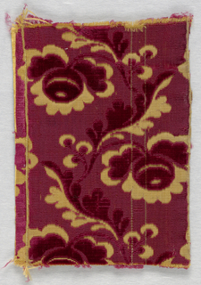 Fragment of cut and uncut dark pink velvet in a design of a curving leafy vine with flowers on an off-white ground.
