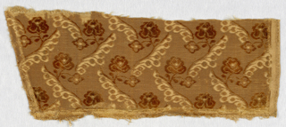 Ciselé velvet in tan with a ground of uncut pile with small scale conventionalized rose in cut pile. Diagonal decorative lines voided in satin ground.
