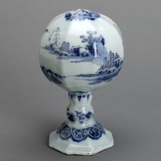 Bulbous wig stand on a stem with octagonal foot. Chinoiserie decoration in cobalt. Blue tinted tin ground.
