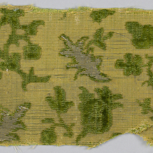 Fragment of green cut and uncut velvet on a yellow silk and metallic ground with some details in silver metal thread brocade. Design of tiny flowering branches in horizontal rows alternately leaning left and right.