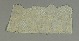 Fragment of a woven linen border showing design of flowers, sprigs and leafy scrolls forming a scalloped edge.