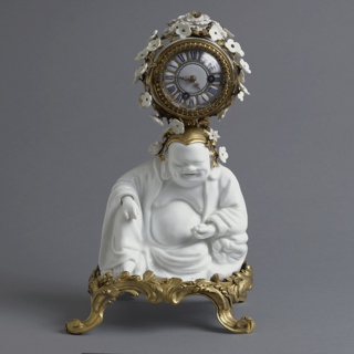 A white porcelain figure of Budai on a gilt bronze four legged base; circular clock in bronze housing covered in small white porcelain flowers on top of  figure's head.