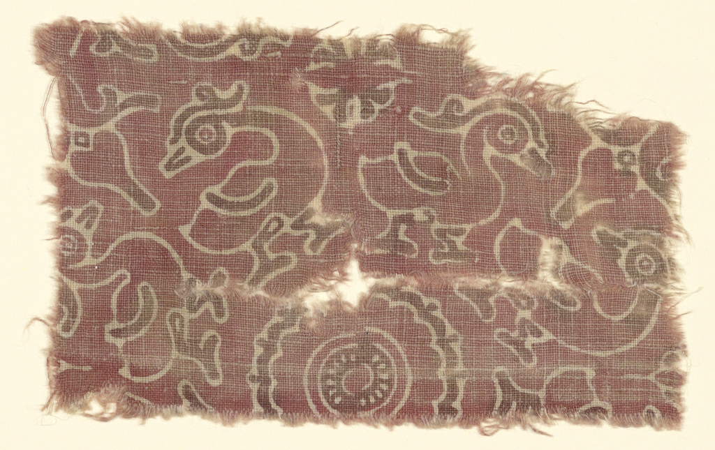 Small section of all-over small repeat of eight ducks or hamsas marching around a 16-lobed rosette representing a lotus; other smaller rosettes in interspaces.  In broad line reserve on deep pink ground; touches of purplish brown - feet, wings, bills, topknots of ducks, parts of rosettes.
