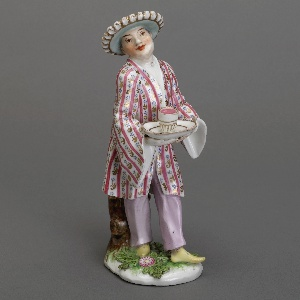 Porcelain figure in decorated hat and jacket serving a drink.
