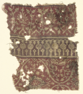 Natural cotton plain cloth ground.  Design in natural and brown on red ground arranged horizontally.  Upper border torch-like motifs and stylized foliate forms.  Center highly conventionalized uprights from lotus motifs.  Below, arabesque, foliage.