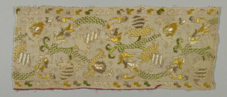 Gauze weave embroidered in yellow, green and brown silks in a variety of stitches. Pattern is scrolling forms with leaves and flowers.