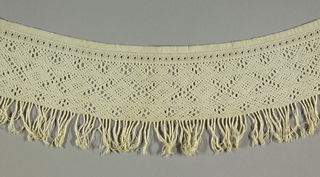 Originally from a towel that was woven and then the ends were braided to form a fringe. The fringe has since been trimmed off the towel. It has a pattern of crosses and quatrefoils.