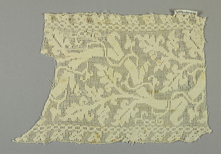 Fragment of a border with a white curving vine on white gauze weave.